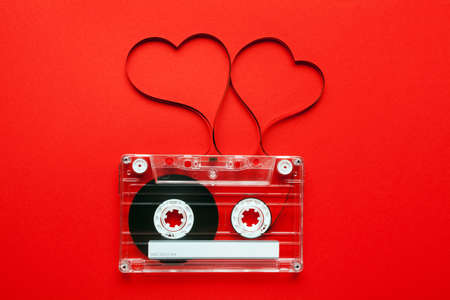 design media love: Vintage audio cassette with loose tape shaping two hearts on red background