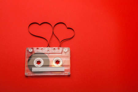 Vintage audio cassette with loose tape shaping two hearts on red