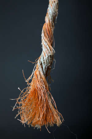 discontinuity: Cut and frayed rope hanging by a thread and ready to break
