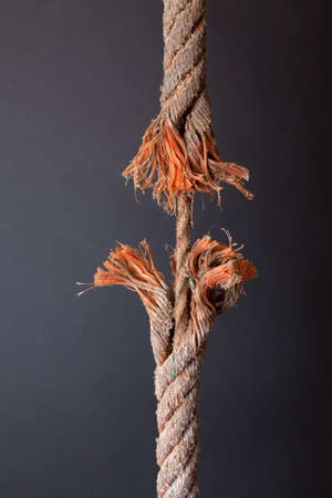 discontinuity: Cut and frayed rope hanging by a thread and ready to break on dark background
