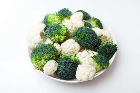 Fresh ripe broccoli piece and cauliflower cabbage vegetables on vintage wooden boards  photo