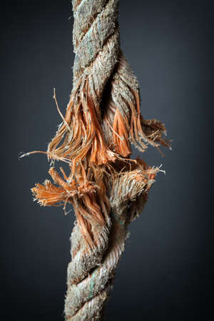 abruption: Cut and frayed rope hanging by a thread and ready to break on dark background
