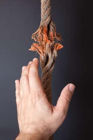 Breaking rope and hand on dark background photo