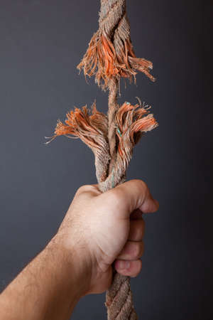abruption: Breaking rope and hand on dark background