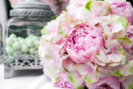 Bridal bouquet of peonies on bride and groom table at wedding reception Stock Photo