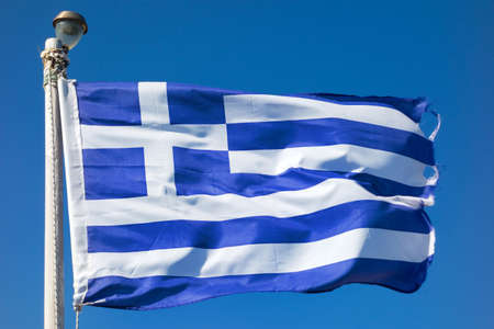 Greece flag waving in the wind over blue sky