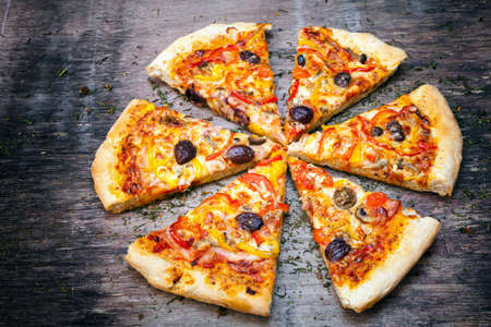 Sliced home made pizza on wooden rustic background  photo