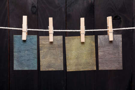 attach: Close up of wooden notes attach to rope with clothes pins on dark wooden background
