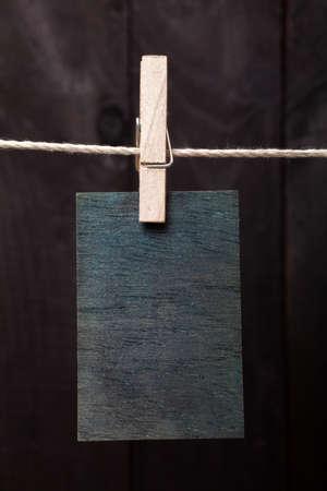 attach?: Cerca de la nota de madera adjuntar a la cuerda con la ropa pin en el fondo de madera oscura Foto de archivo