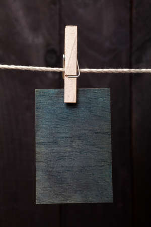 attach: Close up of wooden note attach to rope with clothes pin on dark wooden background