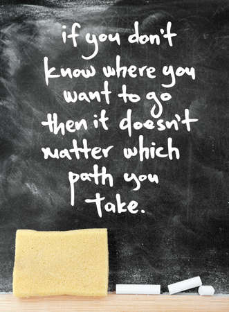 which: IF YOU DONT KNOW WHERE YOU WANT TO GO THEN IT DOESNT MATTER WHICH PATH YOU TAKE quote on a blackboard background Stock Photo