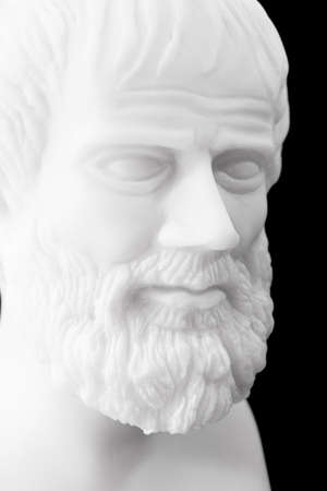 theorist: Greek philosopher Aristotle (384–322 B.C.E.) sculpture isolated on black background  Stock Photo
