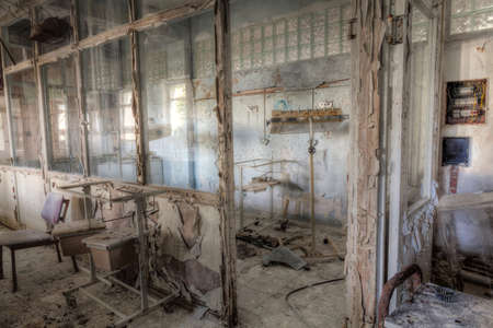 decrepit: Interior of an abandoned building with rubble and debris. Deserted old hospital