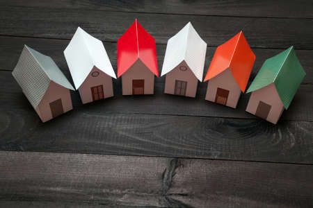 Papercraft Houses in a row on a dark wooden surface Stock Photo