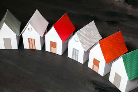 dwelling: Papercraft Houses in a row on a dark wooden surface Stock Photo