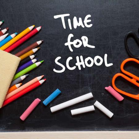 Time for school. School tools around. Blackboard background. photo