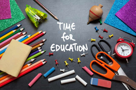 Time for education. School tools around. Blackboard background. photo