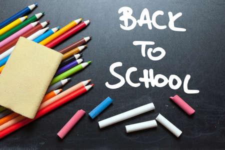 Back to school. School tools around. Blackboard background.