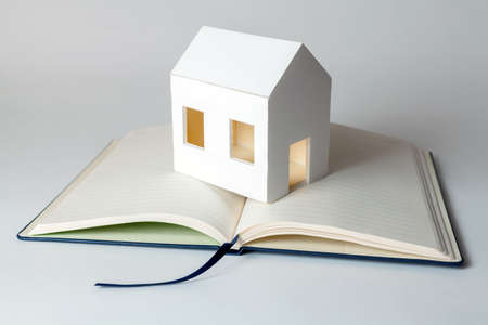 Requirements of the house. Paper house on memorandum block Stock Photo