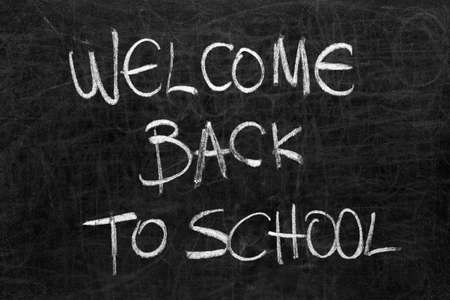 Written welcome back to school on the blackboard with white chalk