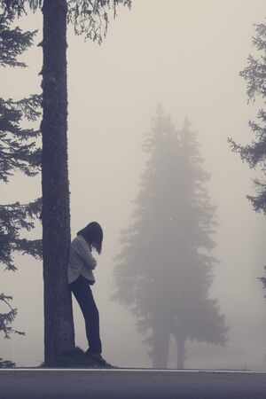 Depressed woman leaning against tree in fog