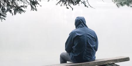 Depressieve man zit op bankje in jack met capuchon Stockfoto