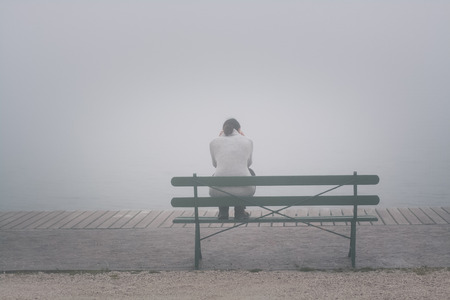 A lonely woman sitting alone on the bench, lost in thought on foggy day