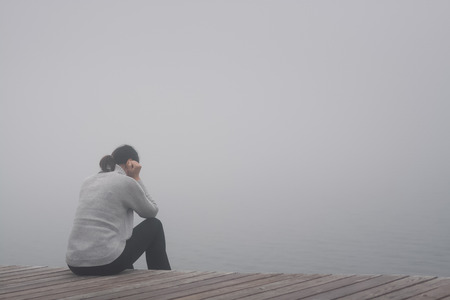 Young woman sits on the edge of a wooden bridge and sadly gets lost in thought in the fog