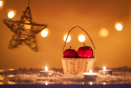 Christmas background with basket of apples, candles, snow, stars and bokeh lights