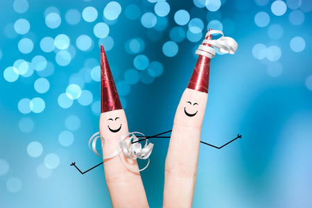 Smiling fingers with red hats on a blue background