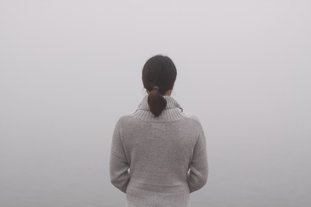 Back view of an attractive woman on a foggy day Stock Photo