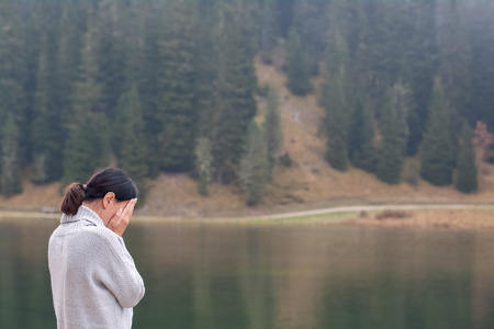 Anonymous woman standing by water and woods and crying back view Stock Photo