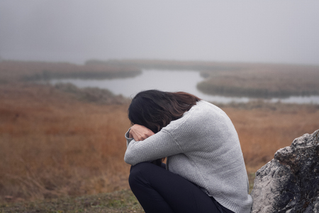 Young woman leaning against the stone with arms crossed in front of the face, gloomy mood Stock Photo - 93796655