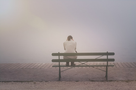 Anonymous woman is sitting on a bench on a foggy day Stock Photo