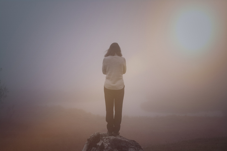 Anonymous person is standing at the top of a mountain on a foggy day Stock Photo - 95209561