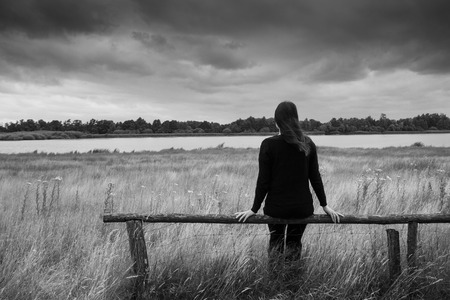 Young sad woman is sitting on a wooden fence and glazing into the distance. Monochrome portrait.