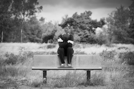 Young woman sitting on a bench. Monochrome portrait. Stock Photo