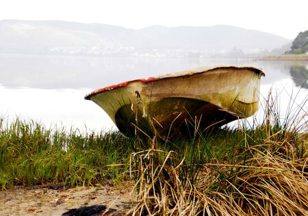 A lonely row boat moored on a grassy bank photo