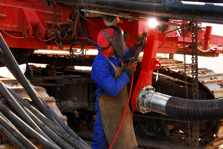 earth moving: A blue collar worker welding earth moving equipment on a construction site