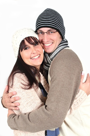 Young couple hugging in winter clothes on white background photo