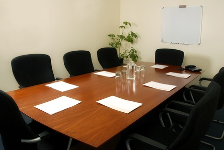 Boardroom table with places set ready for a meeting photo