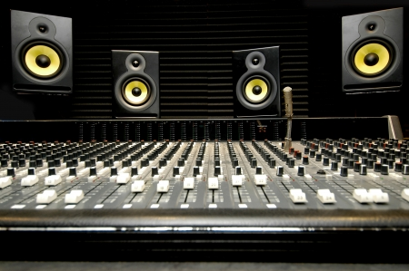 audio speaker: Low angle shot of a mixing desk with yellow and black speakers