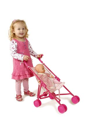 doll: Little girl dressed in pink pushing a doll in a pram