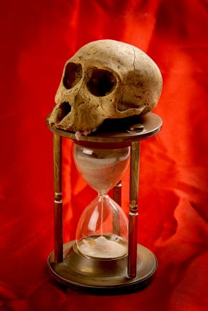 sand timer: Hourglass showing falling sand with skull symbolizing life on a red background