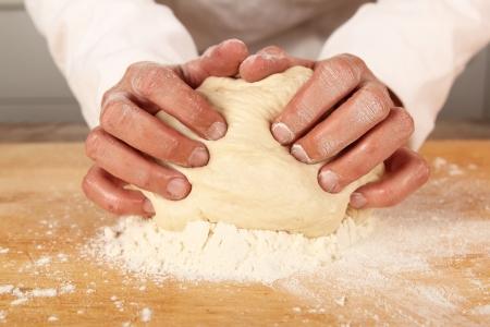 haciendo pan: Primer plano de las manos de los panaderos amasar un trozo de masa
