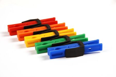 Unusual multicolored clothes pegs in a diagonal line on a white background photo