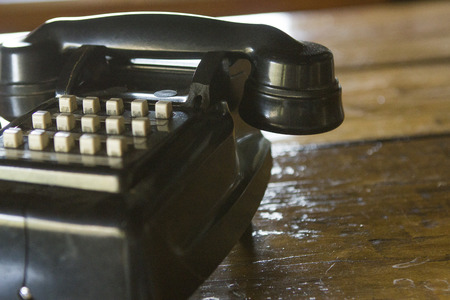 bygone: Black vintage telephone on wooden surface with copy space