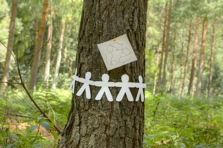 hands holding tree: Recycle sign with paper men holding hands on a tree symbolizing a group effort to recycle