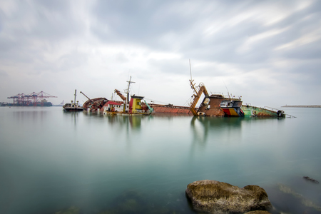 sinking: A sunken wreck rusting into the sea - Stock Image