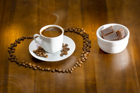 white cup hot Turkish coffee  and scattered coffee grains - Stock Image